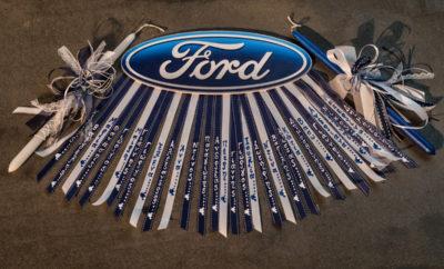 • Οι εργαζόμενοι της Ford στην Ελλάδα δημιουργούν μία πρότυπη γραμμή συναρμολόγησης και προσφέρουν Πασχαλινές Λαμπάδες στα παιδιά του Χατζηκυριάκειου • Η διαδικασία κατασκευής τους δεν ήταν τελικά τόσο δύσκολη όσο φαινόταν, ή μήπως ήταν; Οι εργαζόμενοι της Ford στην Ελλάδα συγκεντρώθηκαν για καλό σκοπό εκείνο το απόγευμα. Στόχος ήταν να συνεργαστούν δυναμικά για την παραγωγή Πασχαλινών Λαμπάδων, ως προσφορά αγάπης για τα παιδιά που φιλοξενούνται στο Χατζηκυριάκειο Ίδρυμα. Θα ήταν πιο εύκολο να αγοραστούν και να μη «ασχοληθεί» κανένας, όμως ο στόχος εκτός από την προσφορά ήταν και το δημιουργικό κομμάτι, όπως και η σύσφιξη των σχέσεων μεταξύ των εργαζομένων. Για το λόγο αυτό επιστρατεύτηκε η παλιά συνάδερφος στη Ford, η Στέλλα Δερτιμάνη που εδώ και αρκετά χρόνια έχει ειδικευτεί στην παραγωγή χειροποίητων κατασκευών. «Εργάστηκα στη Ford για 15 ολόκληρα χρόνια. Όταν είσαι μέρος μιας ομάδας για τόσο μεγάλο χρονικό διάστημα, δένεσαι με τους συνάδελφούς σου και αναπτύσσεις μαζί τους φιλικές σχέσεις», δήλωσε η Στέλλα Δερτιμάνη, βοηθός λογιστή στη Ford Motor Ελλάς από το 1998 έως το 2013. «Όταν μου προτάθηκε να βοηθήσω στην κατασκευή Πασχαλινών λαμπάδων για το Χατζηκυριάκειο ίδρυμα, ενθουσιάστηκα και σκέφτηκα πως θα ήταν όμορφο να βοηθήσω τους παλιούς μου φίλους για το σκοπό αυτό». Η «γραμμή συναρμολόγησης» στήθηκε και η Στέλλα Δερτιμάνη δίνει οδηγίες στους παλιούς της συνάδελφους για το πώς θα φτιαχτούν οι λαμπάδες. Ιδανικός χώρος για να στηθεί η «Πρότυπη Γραμμή Συναρμολόγησης Πασχαλινών Λαμπάδων» δεν ήταν άλλος από το Κέντρο Εκπαίδευσης της Ford, στον Γέρακα. Εκεί έδωσαν ραντεβού όλοι οι εργαζόμενοι της Ford αφήνοντας για λίγες ώρες το γραφείο τους. Στην κεντρική αίθουσα στήθηκαν 4 μεγάλα τραπέζια, όσα και τα διαφορετικά σχέδια των λαμπάδων. Σε κάθε τραπέζι υπήρχαν δείγματα από τις λαμπάδες που θα έφτιαχνε η κάθε ομάδα καθώς και τα απαραίτητα υλικά. Κορδέλες, κορδόνια, βραχιολάκια, κεριά, άσπρα και μπλε, όλα στα χρώματα της Ford. Όλα τα απαραίτητα υλικά ήταν τοποθετημένα 