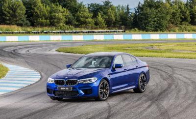 Η νέα BMW M5 (κατανάλωση μικτού κύκλου: 10,5 l/100 km*, εκπομπές CO2 στο μικτό κύκλο: 241 g/km *) προάγει τη BMW M GmbH σε ένα άλλο επίπεδο, καθώς το sedan υψηλών επιδόσεων αποκτά για πρώτη φορά σύστημα M xDrive AWD. Αυτή η νέα φιλοσοφία δίνει νέα διάσταση στις δυναμικές δυνατότητες της Μ5, αναβαθμίζοντας την καθημερινή πρακτικότητα σε όλες τις οδηγικές συνθήκες. Το νέο αυτοκίνητο έχει τις ρίζες του σε ένα πρωτότυπο – το πολυτελές τετράθυρο business sedan αγωνιστικού στυλ– που πρωτοείδαμε το 1984, με την πρώτη BMW M5. Το M xDrive που δημιούργησε η BMW M GmbH είναι το πιο συναρπαστικό σύστημα AWD στην κατηγορία υψηλών επιδόσεων. Χρησιμοποιεί κεντρικό κιβώτιο τετρακίνησης με πολύδισκο συμπλέκτη και κατανέμει την ισχύ μεταβλητά μεταξύ εμπρός και πίσω άξονα, ανάλογα με τις απαιτήσεις. Ένα ακόμα συστατικό κορυφαίας πρόσφυσης σε όλες τις οδικές και καιρικές συνθήκες είναι το Active M Differential στον πίσω άξονα, που επίσης λειτουργεί μεταβλητά και προσφέρει ποσοστό εμπλοκής από 0 έως 100%. Ο χαρακτήρας του M xDrive ρυθμίζεται σύμφωνα με τις επιθυμίες του οδηγού, που μπορεί να επιλέξει από πέντε διαφορετικά σεταρίσματα, ανάλογα με τους συνδυασμούς των DSC modes (DSC on, MDM, DSC off) και των M xDrive modes (4WD, 4WD Sport, 2WD). Στο βασικό σετάρισμα, με ενεργοποιημένο το DSC (Dynamic Stability Control) και 4WD, το σύστημα επιτρέπει ελαφρά ολίσθηση των πίσω τροχών κατά την επιτάχυνση στην έξοδο των στροφών – επομένως παίζει σημαντικό ρόλο στη σπορ ευελιξία της νέας BMW M5. Στο M Dynamic mode (MDM, 4WD Sport), το M xDrive επιτρέπει ελεγχόμενες υπερστροφές ισχύος (drifts). Τα τρία M xDrive modes με το DSC απενεργοποιημένο προορίζεται για ενθουσιώδεις οδηγούς και κυρίως για χρήση στην πίστα. Εδώ, ο οδηγός μπορεί να επιλέξει από τρία σεταρίσματα που περιλαμβάνουν και αμιγή πίσω κίνηση (2WD). Το συγκεκριμένο πρόγραμμα παρέχει δυνατότητα επιλογής της γωνίας ντριφταρίσματος, για γνήσια οδηγική απόλαυση. Τα πλούσια αποθέματα ισχύος της BMW M5 παράγει ένας κινητήρας 4.4L V8 bi-turb
