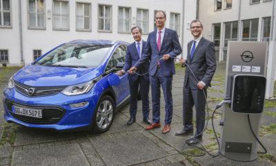 """Μέχρι 1.300 σταθμοί φόρτισης το 2020 ενισχύουν το πακέτο της ηλεκτροκίνησης Εκτενής χρήση ανανεώσιμης ενέργειας και ελάχιστη επέκταση ηλεκτρικού δικτύου Ομάδα έρευνας του RheinMain University μελετά τις συνήθειες των οδηγών προκειμένου να προσδιοριστεί η βέλτιστη θέση των σταθμών φόρτισης Τοπικές αρχές και εκπρόσωποι του επιχειρηματικού και επιστημονικού κόσμου σε μία μοναδική συνεργασία Το Rüsselsheim am Main, η γενέτειρα της Opel θα γίνει """"Ηλεκτρική Πόλη"""". Το Rüsselsheim, η Opel και το RheinMain University «οδηγούν» τις εξελίξεις στην επέκταση της υποδομής φόρτισης για τα ηλεκτρικά οχήματα. Με χρηματοδότηση από το Ομοσπονδιακό Υπουργείο Οικονομικών, θα ξεκινήσει τους επόμενους μήνες η εγκατάσταση περίπου 1.300 σταθμών φόρτισης σε όλη την πόλη. Θα βρίσκονται σε όλες τις περιφέρειες και κατοικημένες περιοχές, στις εγκαταστάσεις της Opel, στην πανεπιστημιούπολη του RheinMain University, σε συγκροτήματα κατοικιών του gewobau Rüsselsheim, σε χώρους στάθμευσης επιλεγμένων supermarket και εμπορικών κέντρων και στις εγκαταστάσεις των δημοτικών Ιατρείων (GPR). Το φιλόδοξο project, για το οποίο οι εταίροι έχουν λάβει χρηματοδότηση ύψους 12,8 εκατομμυρίων Ευρώ περίπου, θα υλοποιηθεί σταδιακά μέχρι το 2020. Μελλοντικά, κάθε δημόσιος σταθμός φόρτισης θα εξυπηρετεί 72 κατοίκους, που μεταφράζεται στην υψηλότερη πυκνότητα σταθμών φόρτισης αναλογικά με τον αριθμό κατοίκων, όχι μόνο στη Γερμανία αλλά και σε όλη την Ευρωπαϊκή Ένωση. Εξάλλου, 400 ακόμα σημεία φόρτισης θα εγκατασταθούν σε ιδιωτικές ιδιοκτησίες – 350 από τα οποία στις εγκαταστάσεις της Opel. Ενδεικτικά, το Αμβούργο, που σήμερα είναι η Νο1 πόλη της Γερμανίας σε υποδομή φόρτισης, έχει 785 δημόσια προσβάσιμα σημεία φόρτισης για 1,8 εκατομμύρια κατοίκους (σύμφωνα με την κατάταξη του Federal Association of Energy and Water Industry). «Η μετάβαση στην ηλεκτρική μετακίνηση δημιουργεί ευκαιρίες για το Rüsselsheim. Η πόλη μπορεί να αναλάβει ηγετικό ρόλο στην ανάπτυξη της υποδομής φόρτισης, των ηλεκτρικών οχημάτων και της ηλεκτρ"""