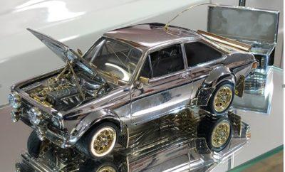 """Εάν τα κοσμήματα σας ελκύουν περισσότερο από την οδήγηση, τότε αυτό είναι το τέλειο αυτοκίνητο για εσάς. Μπορεί να μην το δείτε ποτέ να κυκλοφορεί στο δρόμο, ωστόσο αυτό το Ford Escort αξίζει μία ολόκληρη περιουσία. Πρόκειται για ένα μοναδικό, στην κυριολεξία, μοντέλο υπό κλίμακα 1:25 κατασκευασμένο από πολύτιμα υλικά, όπως το ασήμι, ο χρυσός και τα διαμάντια. Το διαφορετικό αυτό Ford Escort κατασκευάστηκε από το μηδέν με πολύ αγάπη και μπόλικο μεράκι από τον επαγγελματία κοσμηματοπώλη και λάτρη των σπορ αυτοκινήτων, Russell Lord. Ο Lord, έχοντας υπάρξει ιδιοκτήτης 55 αυτοκινήτων Ford Escort κανονικού μεγέθους επί σειρά ετών, ξεκίνησε να δουλεύει πάνω στο εκπληκτικό αυτό """"μοντελάκι"""" πριν από 25 ακριβώς χρόνια, αφιερώνοντας χιλιάδες ώρες για την ολοκλήρωσή του. Το αμάξωμα είναι φτιαγμένο από ασήμι, με το αυτοκίνητο να διαθέτει επίσης χρυσά φρένα και αεροτομή, τροχούς και μεντεσέδες καπό από χρυσό 18 καρατίων, μάσκα από λευκόχρυσο 18 καρατίων, διαμαντένιους προβολείς 0,72 καρατίων, φλας από πορτοκαλί ζαφείρι και φώτα φρένων από ρουμπίνια. Χαρακτηριστικές επίσης λεπτομέρειες της κατασκευής είναι οι περιστρεφόμενες τροχαλίες στο εμπρός τμήμα του κινητήρα, ο πλατινένιος και κινούμενος μοχλός αλλαγής των σχέσεων στο εσωτερικό και τα κρυστάλλινα παράθυρα, για τα οποία ο Russell Lord χρειάστηκε να θρυμματίσει αμέτρητα βάζα προκειμένου να βρει με ακρίβεια τις διατομές κρυστάλλων με την κατάλληλη καμπύλη. «Ήταν ένα χόμπι ζωής, στο οποίο επανερχόμουν κάθε τόσο, αλλά πριν από τρία χρόνια αποφάσισα να το τελειώσω. Γνωρίζω το αυτοκίνητο απέξω κι ανακατωτά. Δεν υπήρχαν κάποια σχέδια, απλά το έφτιαξα εξ αρχής, κομμάτι-κομμάτι», σχολίασε ο Lord, από το Essex της Μ. Βρετανίας. Με το κόστος των υλικών που το απαρτίζουν να ανέρχεται στα 90.000 ευρώ, το διαφορετικό αυτό Ford Escort Mk2 είναι βασισμένο στο εργοστασιακό rally-car που οδηγούσε ο Ari Vatenen στα τέλη της δεκαετίας του '70. Όπως ανακοινώθηκε, η μοναδική αυτή μινιατούρα θα δημοπρατηθεί μέσω του ιστότοπου www.themarket.co.uk σ"""