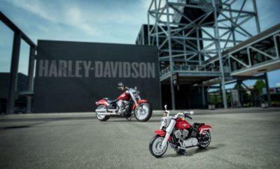 """Σήμερα, η LEGO Group παρουσιάζει το τελευταίο της μοντέλο LEGO® Creator Expert, μία Harley-Davidson® Fat Boy® που θα ταξιδέψει στα καταστήματα LEGO όλου του κόσμου, την 1η Αυγούστου 2019. Αυτό το πιστό αντίγραφο του θρυλικού μοντέλου από το Μιλγουόκι σχεδιάστηκε από τη LEGO σε συνεργασία με τη Harley-Davidson και αντικατοπτρίζει την ομορφιά της πραγματικής μοτοσυκλέτας, με φινιρίσματα, επιφάνειες και σχεδιαστικά στοιχεία που συνδυάστηκαν για τη δημιουργία ενός μοντέλου, όμοιου με το ίδιο το Harley-Davidson® Fat Boy®. Αποτελούμενο από 1,023 κομμάτια, το μοντέλο διαθέτει γεμάτους τροχούς, ρεζερβουάρ τύπου """"δάκρυ"""" ενσωματωμένο ταχύμετρο και διπλά τελικά εξάτμισης. Ολοκληρωμένο, το μοντέλο φτάνει στα 20 εκατοστά πλάτος και 33 εκατοστά μήκος. Διαθέτει αρκετά κινούμενα μέρη που το μετατρέπουν από ένα στατικό μοντέλο σε ένα διασκεδαστικό αντικείμενο πάθους για μικρούς και μεγάλους. Περιστρέψτε τον πίσω τροχό για να φέρετε στη ζωή τα κινούμενα έμβολα του κινητήρα Milwaukee-Eight® και τα διπλά τελικά της εξάτμισης. Γυρίστε το τιμόνι, πατήστε το μοχλό ταχυτήτων, τη μανέτα των φρένων και κατεβάστε το πλαϊνό σταντ για ασφαλή στήριξη. Φινιρισμένο με το αυθεντικό μαύρο και σκούρο κόκκινο χρώμα, με το λογότυπο Harley-Davidson® και στις δύο πλευρές, διαθέτει την πραγματική εμφάνιση και το χρωματισμό Wicked Red του Fat Boy του 2019. Αποτελεί το τέλειο διακοσμητικό για κάθε σπίτι, γραφείο ή οποιοδήποτε άλλο σημείο που εκφράζει το πάθος του ιδιοκτήτη, για τις μοτοσυκλέτες Harley-Davidson®. """"Το να φέρνεις στη ζωή αυτή τη μοτοσυκλέτα Harley-Davidson® με """"τουβλάκια"""" είναι συναρπαστικό, αναφέρει ο Διευθυντής Σχεδιασμού της LEGO Group, Mike Psiaki. """"Αυτό το μοντέλο, πραγματικά αιχμαλωτίζει τη μοναδική σχεδίαση, την προηγμένη τεχνολογία και την έμφαση στη λεπτομέρεια αυτής της θρυλικής μοτοσυκλέτας, προσφέροντας μια μοναδική εμπειρία κατασκευής, αλλά και ένα υπέροχο συλλεκτικό αντικείμενο πάθους για τους φίλους των Harley-Davidson® και LEGO, όλων των ηλικιών."""" """"Είναι εξαιρετικά συναρπαστική"""