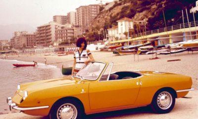"""Η οδήγηση με ένα ανοικτό αυτοκίνητο αποτελεί μία μοναδική εμπειρία. Με μεσογειακό ταπεραμέντο η Fiat προσέφερε πάντα μοντέλα που επέτρεπαν στον οδηγό και τους επιβάτες να βρεθούν σε απόλυτη επαφή με τη φύση. Αυτά είναι τα 10 πιο χαρακτηριστικά παραδείγματα από τα ανοικτά Fiat. Τα μοντέλα με ανοιγόμενη οροφή αποτελούν μια ιδιαίτερη κατηγορία στο χώρο του αυτοκινήτου. Convertible, Cabrio, Spider, Targa, διθέσια ή τετραθέσια, με υφασμάτινη ή μεταλλική οροφή, τα ανοικτά αυτοκίνητα προσφέρουν μια ξεχωριστή εμπειρία οδήγησης σε κάθε εκδοχή τους. Λιγότερο πρακτικά και συνήθως ακριβότερα από τις αντίστοιχες συμβατικές εκδόσεις, τα ανοικτά αυτοκίνητα δεν επιλέγονται με τη λογική, αλλά με το συναίσθημα και την απόλαυση που προσφέρουν. Άλλα με σπορ χαρακτήρα και αλλά με πιο χαλαρή διάθεση, τα παρακάτω ανοικτά μοντέλα της Fiat δημιούργησαν το δικό τους μύθο προσφέροντας την αίσθηση του αιώνιου καλοκαιριού σε εκατομμύρια ανθρώπους σε όλο τον κόσμο. (1) 1200 Spider - 1957 Το διθέσιο 1200 Spider εκτός από τον αρμονικό εξωτερικό σχεδιασμό ξεχώρισε και για μία ιδιαίτερη καινοτομία. Τα καθίσματα μπορούσαν να περιστραφούν κατά τον κατακόρυφο άξονα επιτρέποντας την ευκολότερη είσοδο και έξοδο για τον οδηγό και τον επιβάτη. Ήταν μία λύση που εκτιμήθηκε ιδιαίτερα από τις γυναίκες που πλέον μπορούσαν να απολαμβάνουν ένα σπορ αυτοκίνητο χωρίς να ανησυχούν ότι θα ταλαιπωρήσουν το φόρεμα τους. (2) 500 Jolly """"Spiaggina"""" - 1958 Εξαρχής το Fiat 500 του 1957 σχεδιάστηκε με ανοιγόμενη υφασμάτινη οροφή έτσι ώστε να κάνει οικονομία στο βάρος και την ποσότητα μετάλλου, αλλά παράλληλα και να προσφέρει σε όσο το δυνατόν περισσότερο κόσμο τη χαρά της οδήγησης ενός cabrio. Η έκδοση Jolly που έμεινε γνωστή με το παρατσούκλι """"Spiaggina"""" πήγε ένα βήμα παραπέρα. Το κατασκευασμένο από την Carrozzeria Ghia Jolly επέτρεπε στους τέσσερις επιβαίνοντες να βρίσκονται σε απόλυτη επαφή με το τοπίο, ενώ η κατασκευασμένη από ψάθα επένδυση των καθισμάτων σήμαινε ότι μπορούσαν να ταξιδεύουν με βρεγμένα μαγιό χωρίς καμία"""