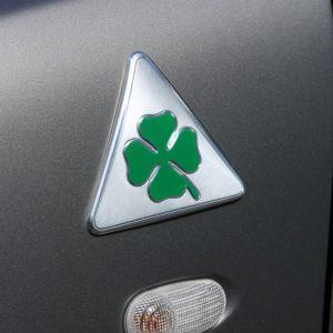 Είναι γνωστό ως το λογότυπο που φέρουν οι κορυφαίες εκδόσεις των μοντέλων της Alfa Romeo, αλλά και τα αγωνιστικά της αυτοκίνητα. Η ιστορία όμως πίσω από το τετράφυλλο πράσινο τριφύλλι (Quadrifoglio Verde) είναι αυτή που αποκαλύπτει γιατί το συγκεκριμένο λογότυπο είναι ένας πραγματικός θρύλος για την Alfa Romeo. Η ημερομηνία γέννηση αυτού του θρύλου τη φετινή χρονιά συνέπεσε με τον αγώνα της Formula 1 στη Monza. H ιστορία της Alfa Romeo είναι άρρηκτα συνδεδεμένη με το χώρο των αγώνων. Από την ίδρυση της εταιρείας το 1910, οι αγώνες αποτέλεσαν αναπόσπαστο κομμάτι της λειτουργίας της, συμβάλλοντας ουσιαστικά στην τεχνολογική πρωτοπορία και την εξέλιξη των αυτοκινήτων παραγωγής. Οι πολυάριθμες επιτυχίες που ήρθαν από τις πρώτες συμμετοχές και συνεχίζονται μέχρι σήμερα δημιούργησαν μία τεράστια παράδοση ενισχύοντας σημαντικά την εικόνα της εταιρείας. Τα αυτοκίνητα με τα οποία συμμετέχει η Alfa Romeo στους αγώνες ξεχωρίζουν, εκτός των άλλων και χάρη στο Quadrifoglio Verde, το τετράφυλλο τριφύλλι που αποτελεί το σήμα κατατεθέν των αγωνιστικών Alfa Romeo, αλλά και των κορυφαίων εκδόσεων των μοντέλων παραγωγής. Το συγκεκριμένο λογότυπο χρησιμοποιήθηκε για πρώτη φορά το 1923 σε μία από τις τέσσερις Alfa Romeo RL που πήραν μέρος στον αγώνα του Targa Florio στη Σικελία. Η ομάδα των οδηγών αποτελούνταν από τους Giulio Masetti, Antonio Ascari, Ugo Sivocci και τον Enzo Ferrari! Ο Ugo Sivocci -ο οποίος είχε προτείνει τον Ferrari για οδηγό της ομάδας- παρά την τεράστια εμπειρία του, λόγω αρκετών ατυχιών είχε δημιουργήσει τη φήμη του «αιώνιου δεύτερου». Σε μια απόπειρα να ξορκίσει την κακή του τύχη, ο Sivocci ζωγράφισε στη γρίλια του αγωνιστικού του ένα λευκό τετράγωνο που περιέκλειε ένα τετράφυλλο τριφύλλι. Προς το τέλος του αγώνα η ιδέα του Sivocci δεν έδειχνε να μπορεί να σπάσει την κακή παράδοση, αφού ο ιταλός οδηγός ήταν -για ακόμα μία φορά- δεύτερος με διαφορά από τον πρώτο Ascari. Τότε όμως και μόλις διακόσια μέτρα από τον τερματισμό, η Alfa Romeo του Ascari βγήκε εκτός. Οι μη
