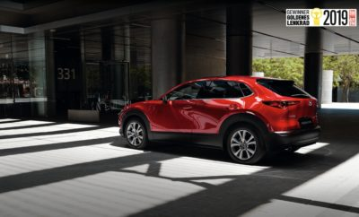 """Το Mazda CX-30 είναι ο νικητής του βραβείου 'Golden Steering Wheel' για το 2019, επικρατώντας των ανταγωνιστών του στην κατηγορία SUV/crossover για οχήματα με μήκος έως 4,4μέτρα. Το ολοκαίνουργιο μικρομεσαίο SUV κερδίζει έτσι το πρώτο του βραβείο σε έναν από τους σημαντικότερους διαγωνισμούς επιλογής αναγνωστών της αυτοκινητοβιομηχανίας. Το βραβείο παρέλαβε ο πρόεδρος της Mazda Motor Europe, Yasuhiro Aoyama σε εκδήλωση που πραγματοποιήθηκε πριν λίγες μέρες στο Βερολίνο. Πρόκειται για το 5ο βραβείο του θεσμού Golden Steering Wheel που κατακτά μέχρι σήμερα η Mazda: Το Mazda 323 το 1985 και το 1989, το Mazda 626 το 1992, και το Mazda2 το 2014. Ο πρόεδρος Aoyama δήλωσε ενθουσιασμένος στην τελετή απονομής: """"Είμαι ιδιαίτερα περήφανος που λαμβάνω σήμερα στο Βερολίνο αυτό το εξαιρετικό βραβείο για το νέο Mazda CX-30. Αυτό αποδεικνύει ότι βρισκόμαστε στο σωστό δρόμο, εστιάζοντας στο design, την τεχνολογική καινοτομία και την αρμονία μεταξύ οδηγού και αυτοκινήτου"""". Εκτός από συγκεκριμένο βραβείο, η Mazda πανηγυρίζει επίσης και για το νέο κινητήρα Skyactiv-X αλλά και για το Mazda3, που βρέθηκαν ανάμεσα στα τρία πρώτα στις κατηγορίες της καινοτομίας και των μικρομεσαίων οχημάτων αντίστοιχα. """"Με τον Skyactiv-X, η Mazda προσφέρει τον πρώτο κινητήρα μαζικής παραγωγής στον κόσμο, που χρησιμοποιεί τεχνολογία αυτανάφλεξης με συμπίεση όπως ένας diesel και τη χρήση μπουζί. Το γεγονός ότι η τεχνολογία αυτή ψηφίστηκε από τους αναγνώστες σαν μία από τις κορυφαίες καινοτομίες στη Γερμανία, μας δίνει μια θετική προοπτική για το μέλλον"""" προσθέτει ο πρόεδρος Aoyama. Ο διαγωνισμός 'Golden Steering Wheel', που πραγματοποιήθηκε για 43η χρονιά, βραβεύει κάθε χρόνο τις καλύτερες καινοτομίες στην αυτοκινητοβιομηχανία. Οι αναγνώστες της εφημερίδας Bild am Sonntag και του περιοδικού Auto Bild, επιλέγουν το καλύτερο από 7 κατηγορίες ανάμεσα από 58 υποψηφία μοντέλα, και ψηφίζουν επίσης για το «Πιο όμορφο αυτοκίνητο» και την «καινοτομία της χρονιάς». Τα μοντέλα που καταλαμβάνουν τις τρείς πρώτες θέσεις """